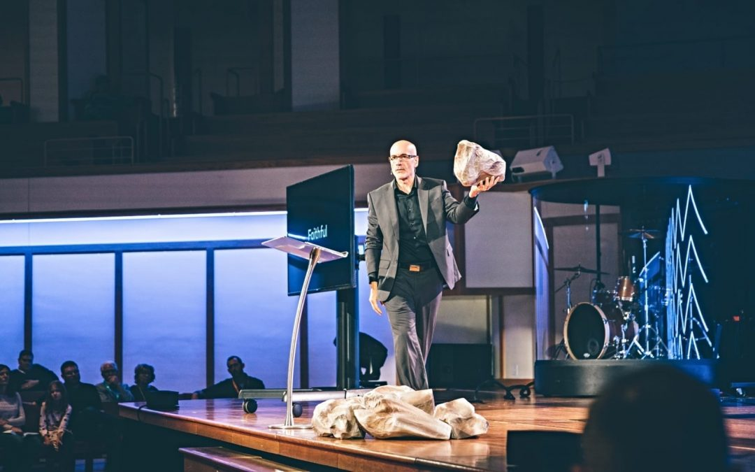 A pastor walking on stage holding a rock