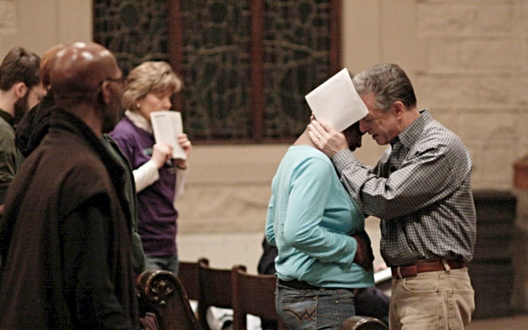 Baptist pastor Joe Phelps praying for a woman during a worship service