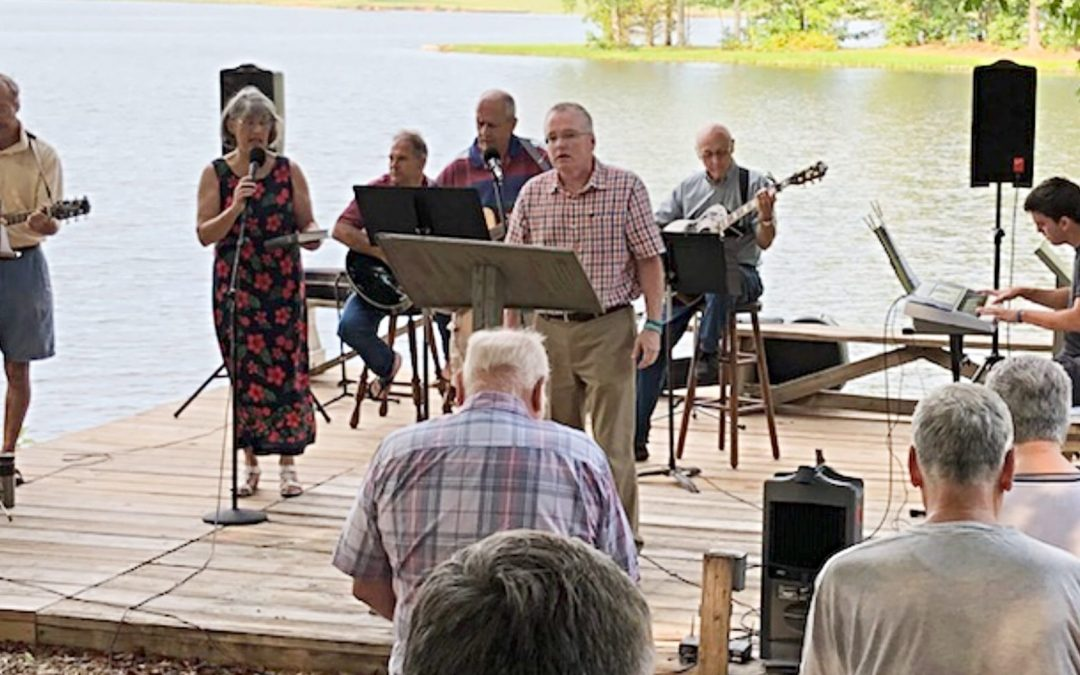 Mickey Robertson leading an outdoor worship service by a lake