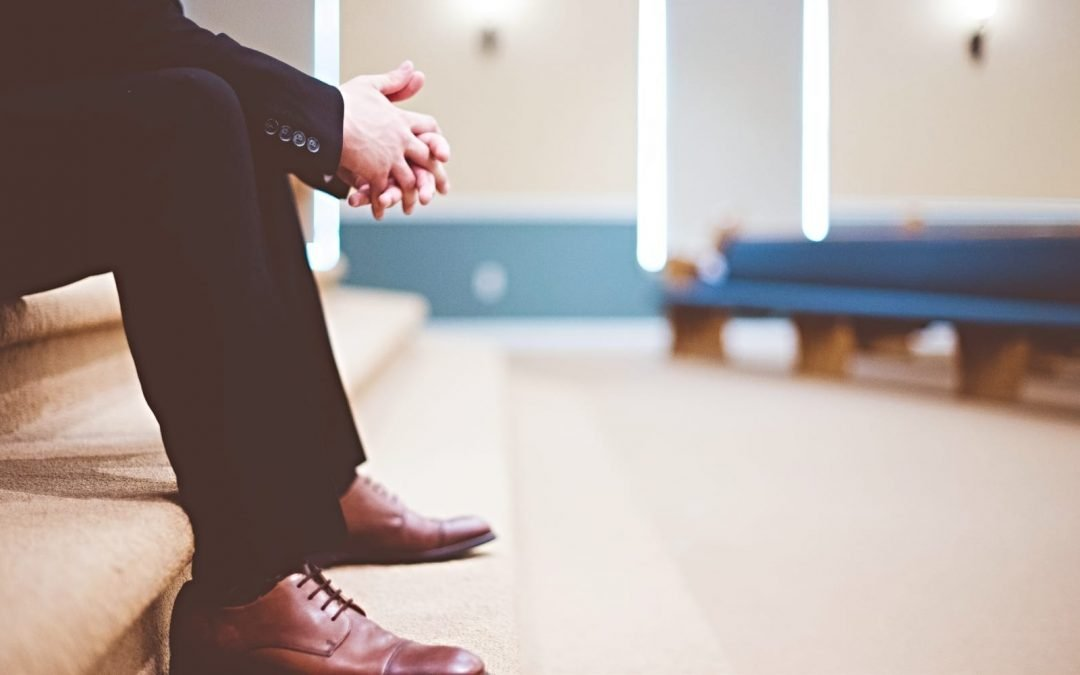 A man dressed in a suit sitting on steps in a church sanctuary