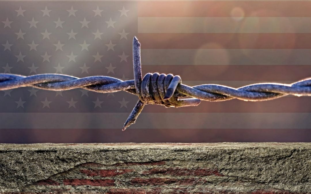 A strand of barbed wire with a a U.S. flag in the background