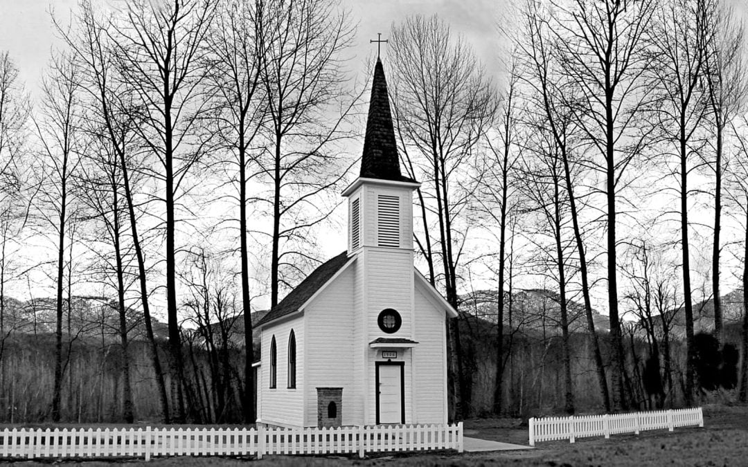 Black and white photo of a church with trees in the background