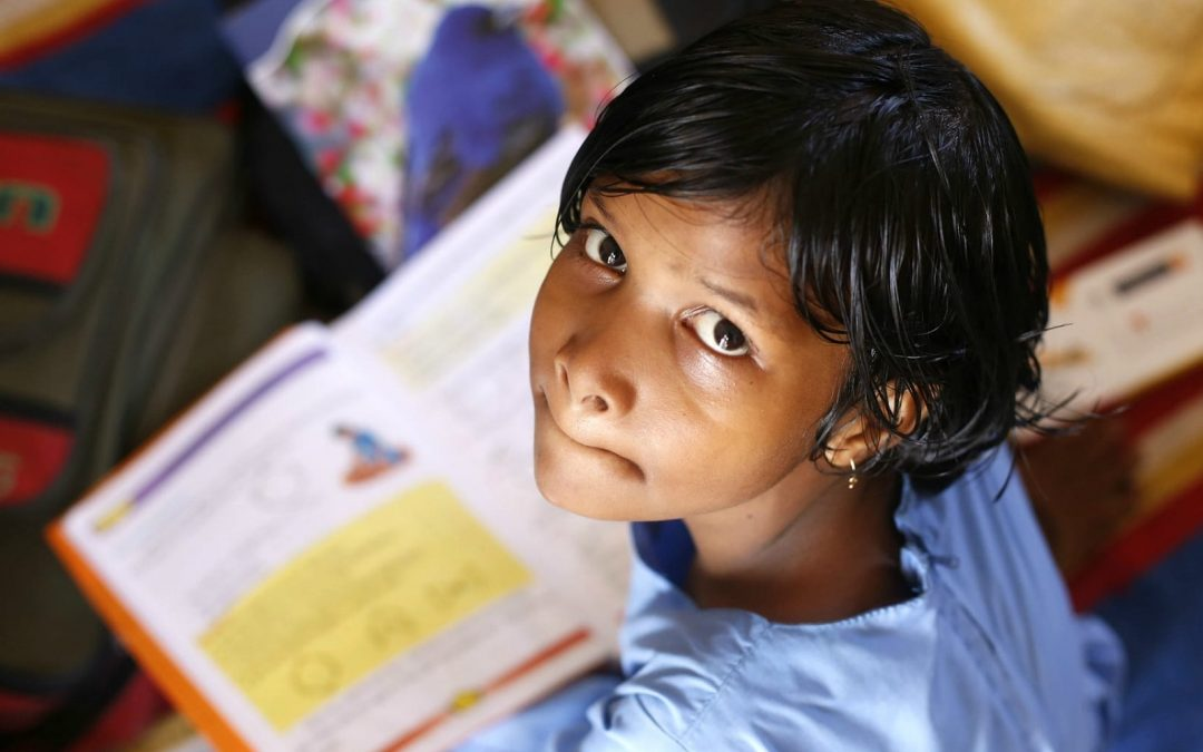 Young girl in school holding a book