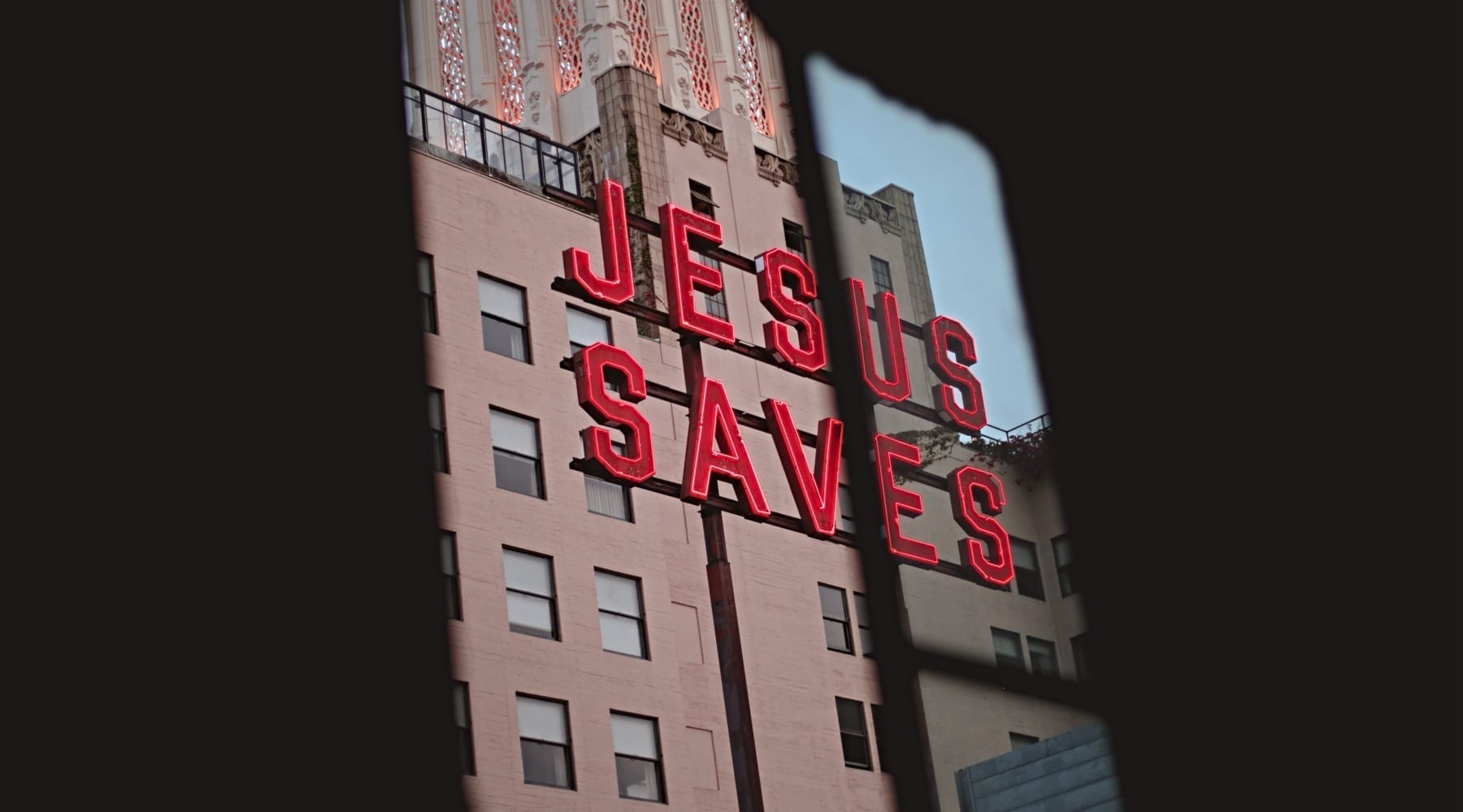Red Jesus Saves sign on metal polls in front of buildings
