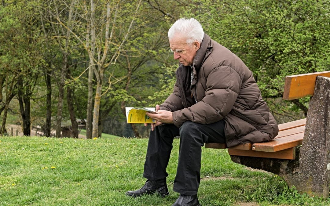 Older man on an outdoor bench reading a book