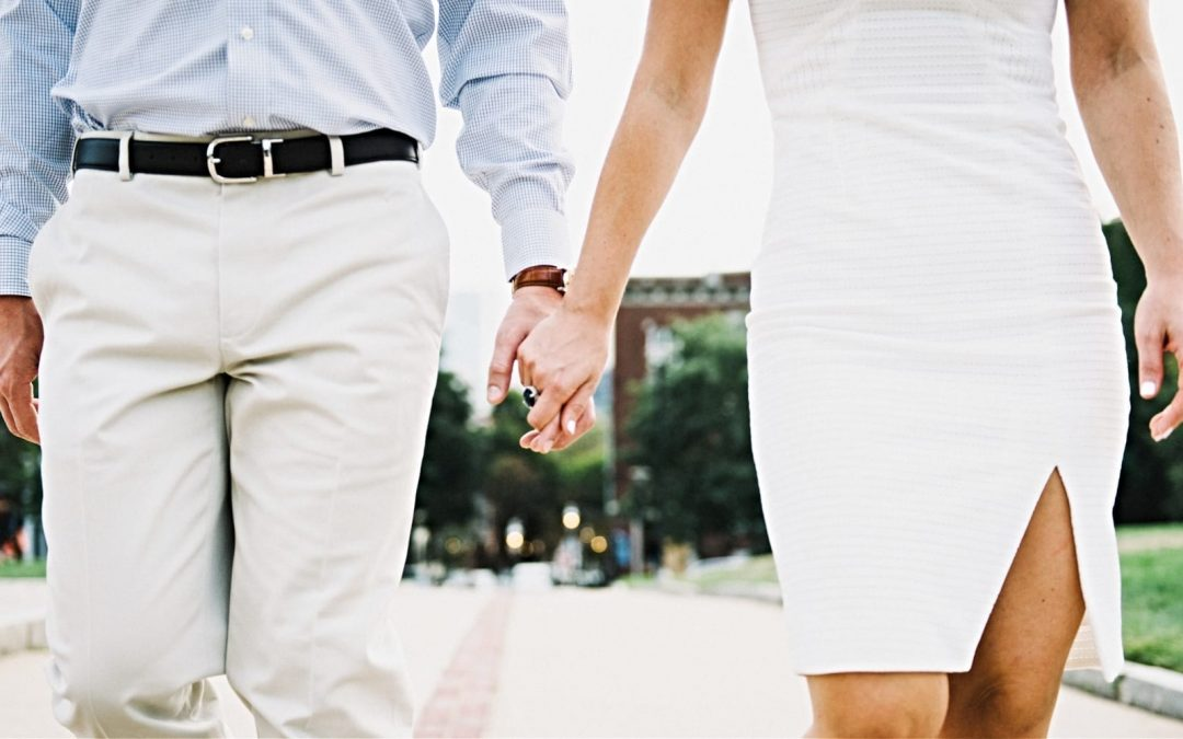 Male, female couple holding hands on a stroll
