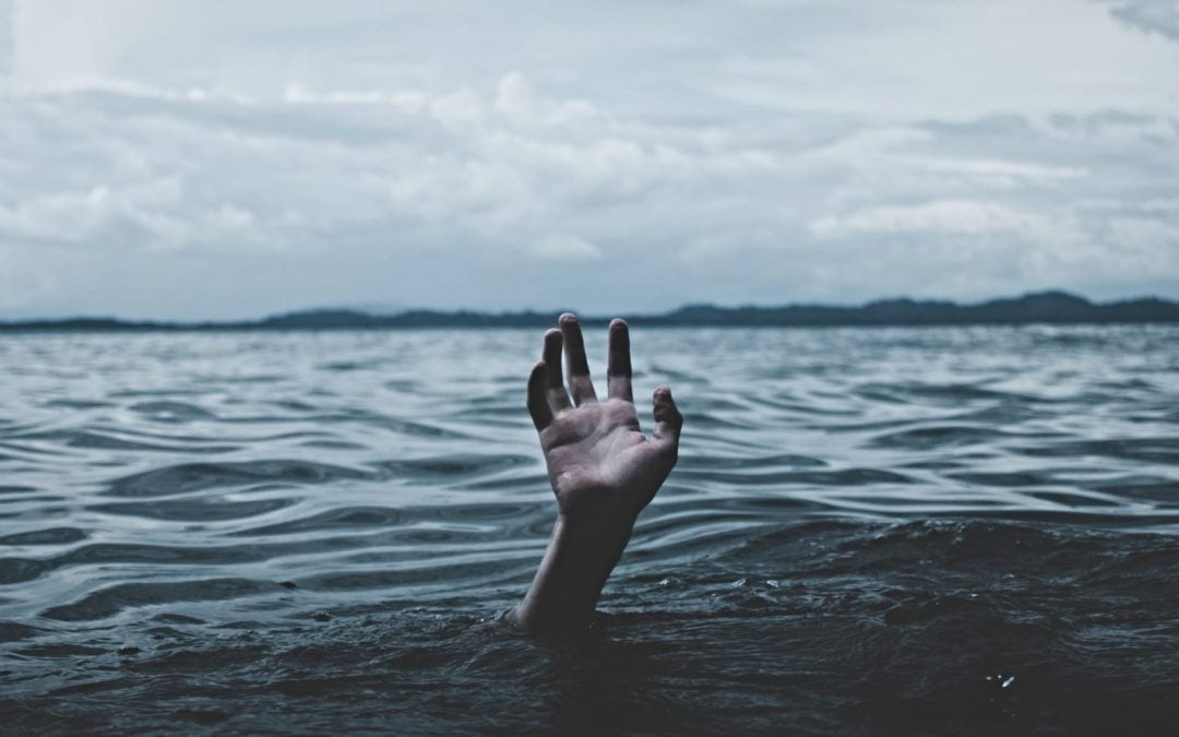 A hand reaching up out of dark waters with a grey sky