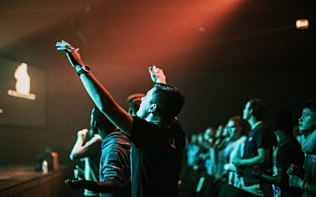 Man in sanctuary, hands raised and worshipping