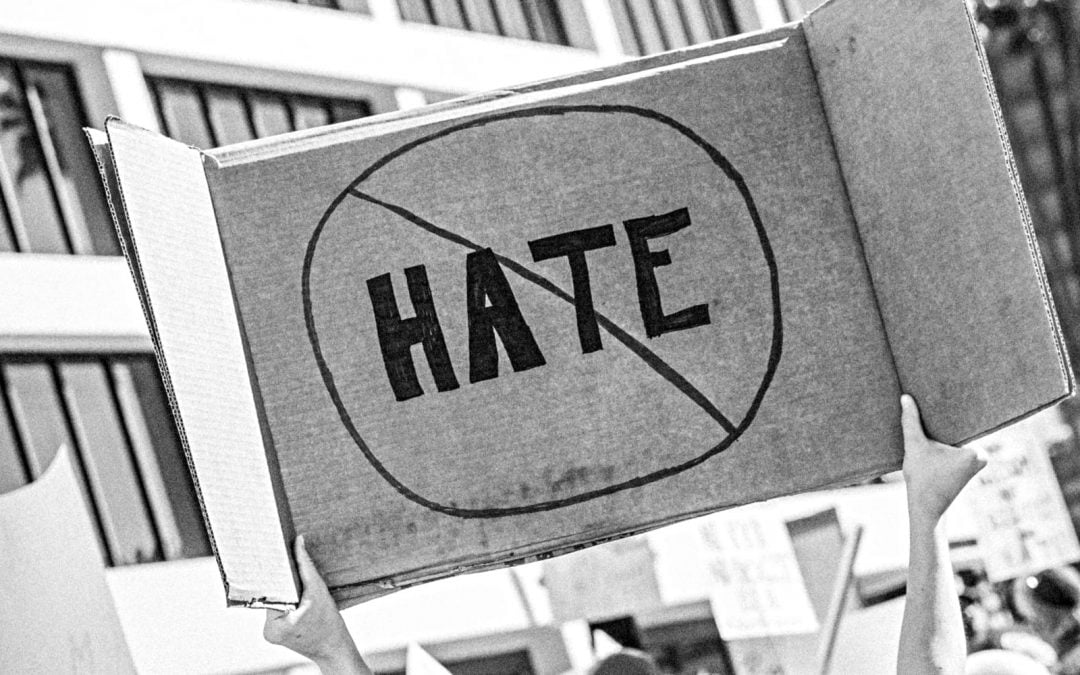 Protester holding up no-hate cardboard sign