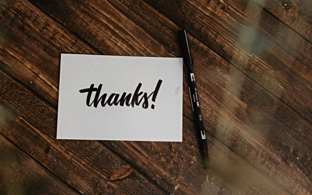 A thanks-you card and pen on table