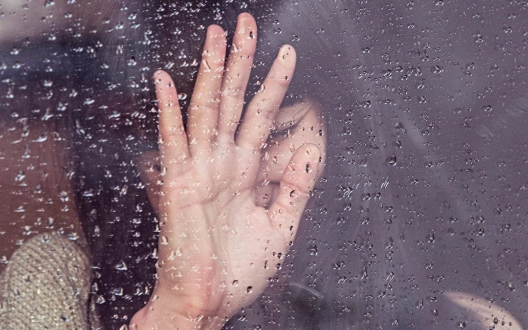Woman's hand on a window covered in water
