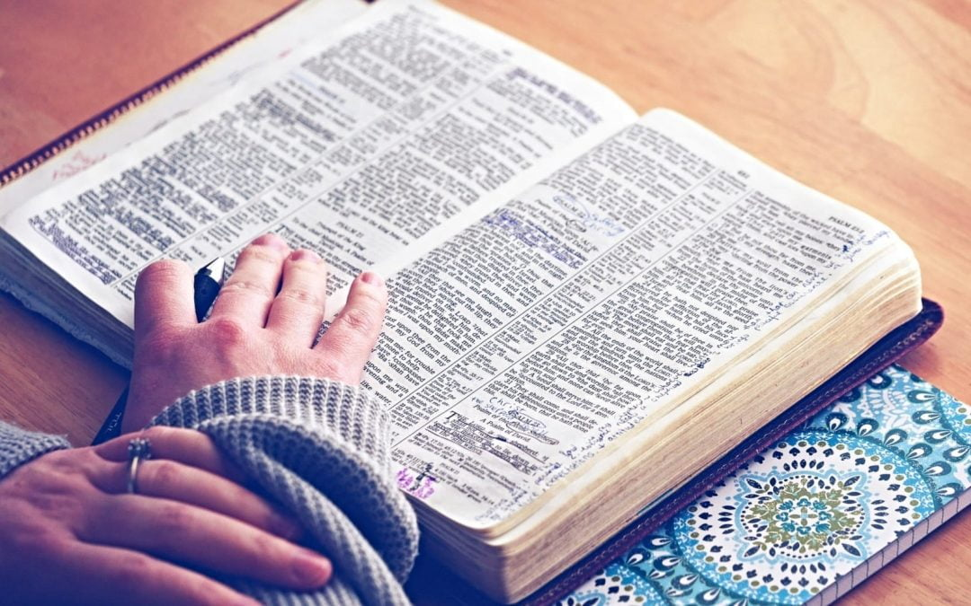 Open Bible on table with two hands touching pages