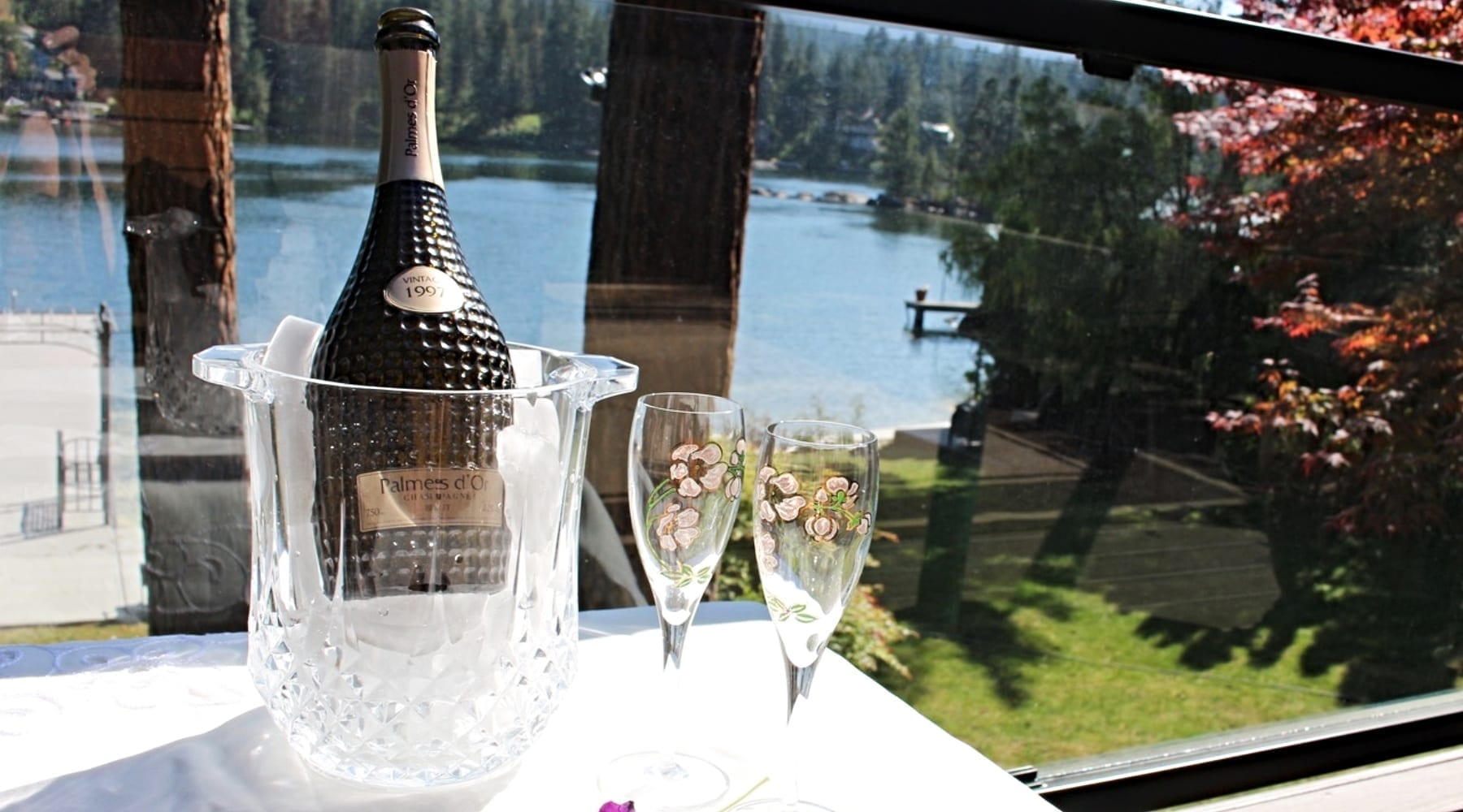 Champagne bottle on table next to two glasses