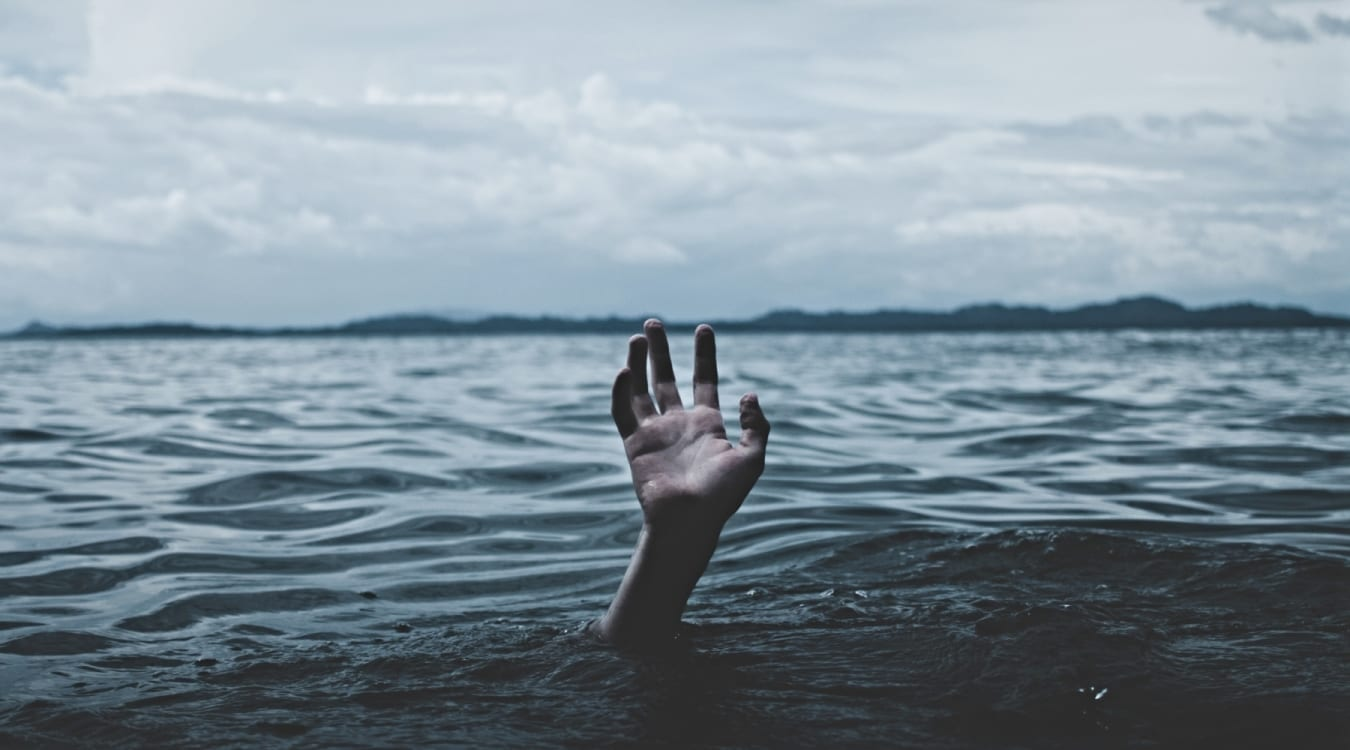 Human hand reaching out of the sea
