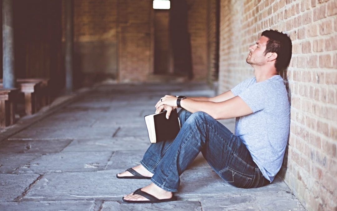 Man holding Bible sitting on street with back against wall