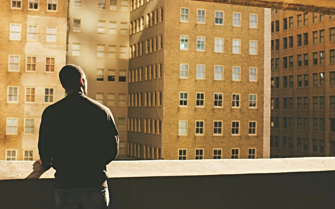 Man on rooftop looking at inner-city high-rise