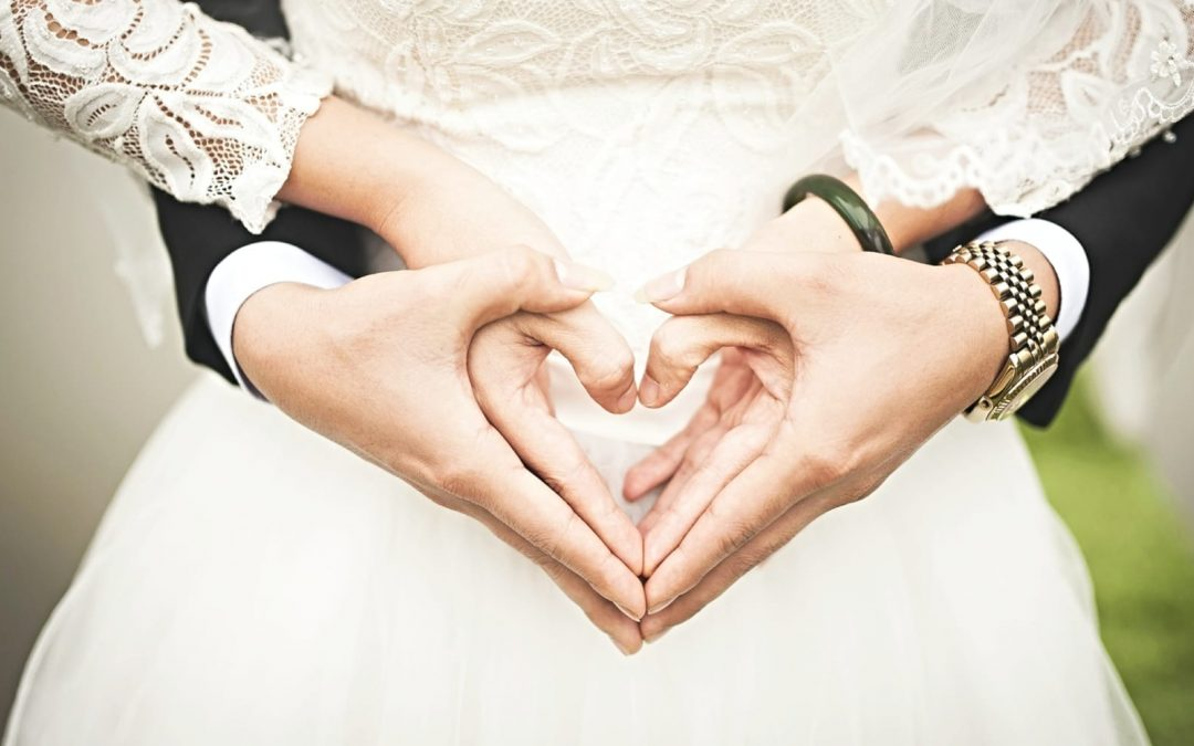 Bride and groom uniting hands to make hearts