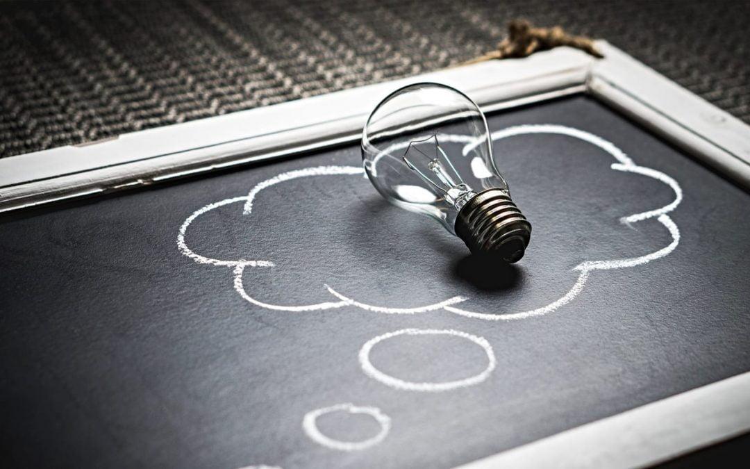 Light bulb inside thought bubble outline on chalkboard
