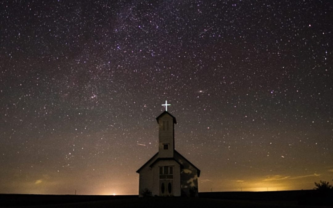 Church with lighted cross at nighttime