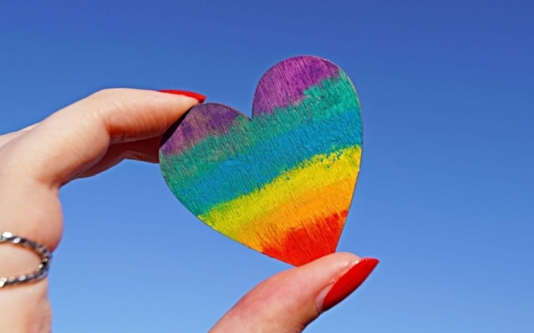 Woman's hand holding rainbow heart