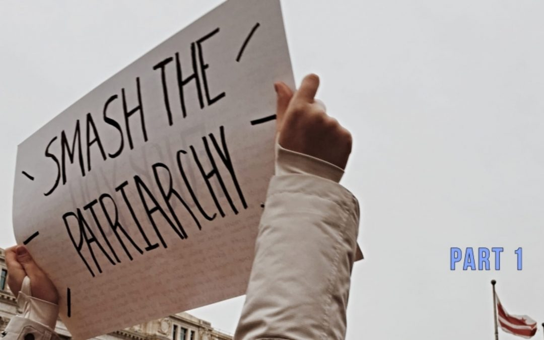 Person carrying sign protesting patriarchy