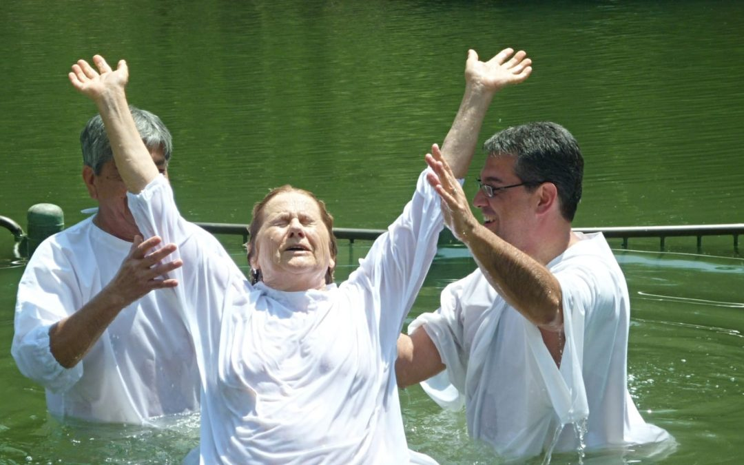 Woman in white robe baptized in river