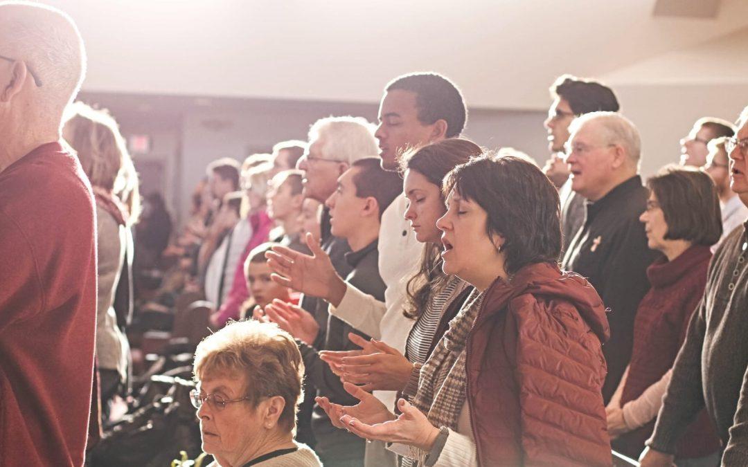 Church members standing and singing in pews