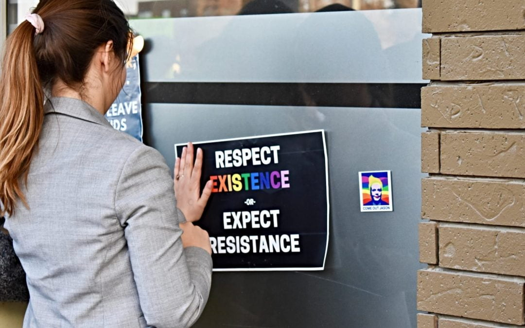 young woman posting sign supporting LGBTQ