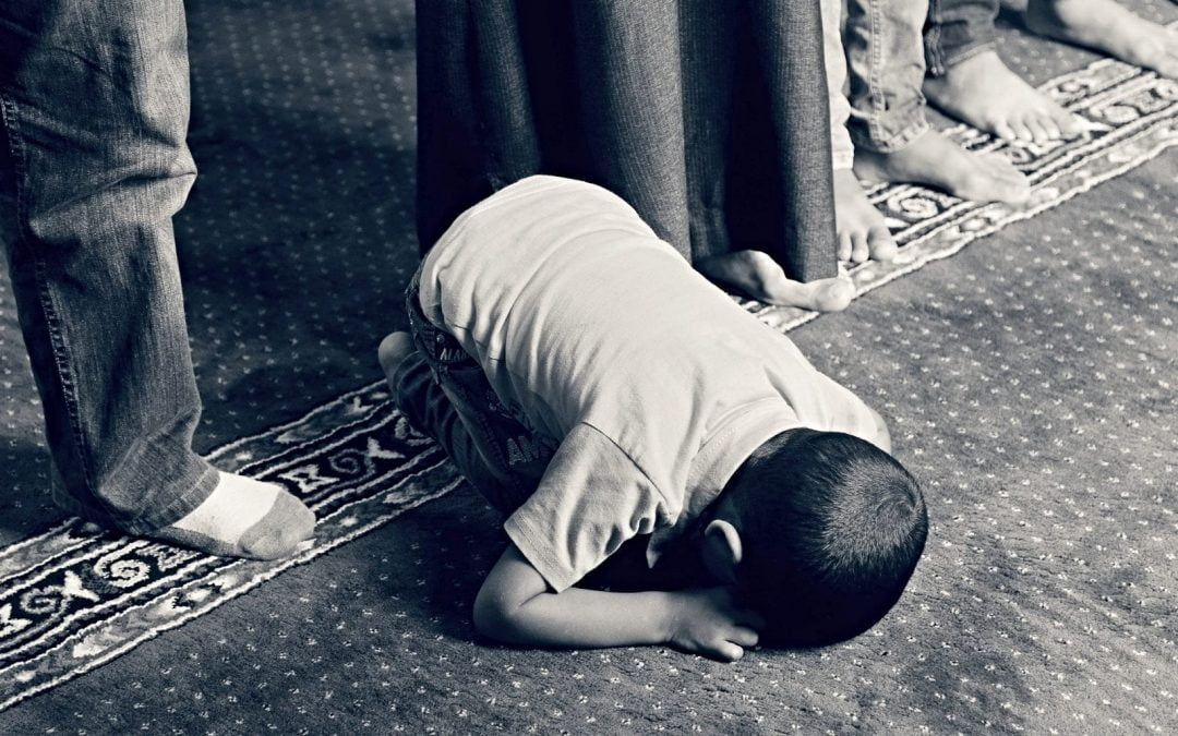 Young Muslim boy kneeling in prayer