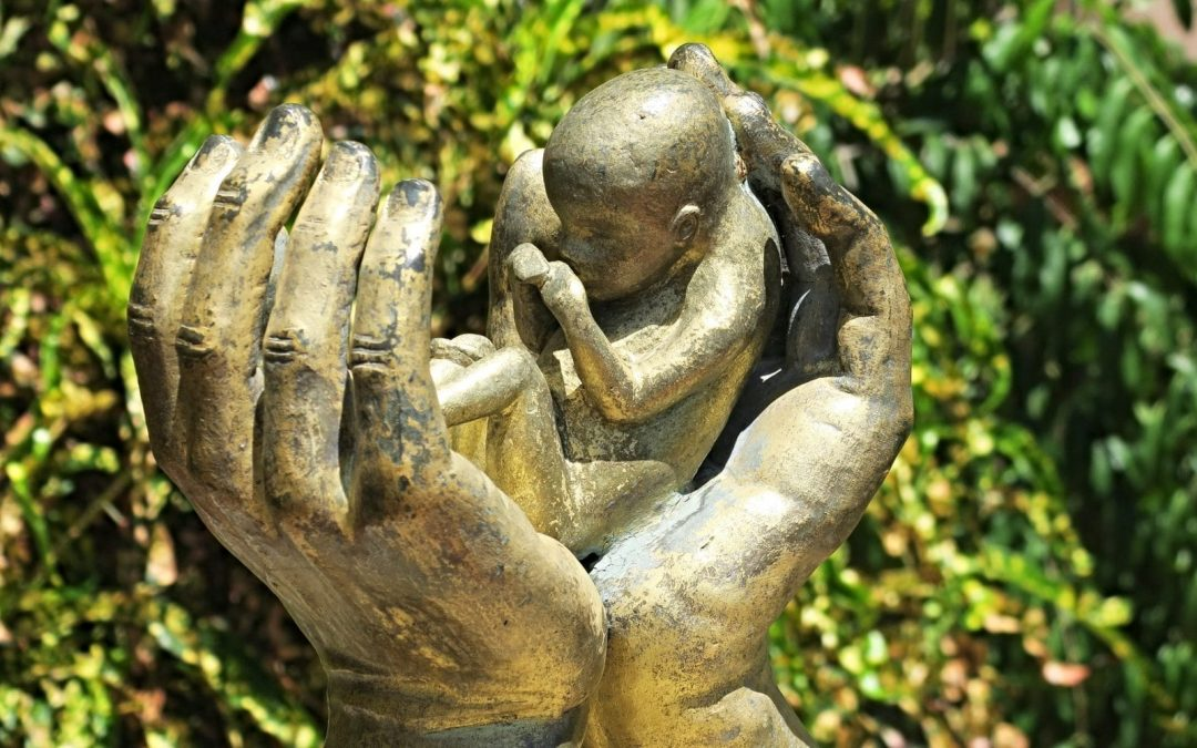 Sculpture of baby between a pair of hands