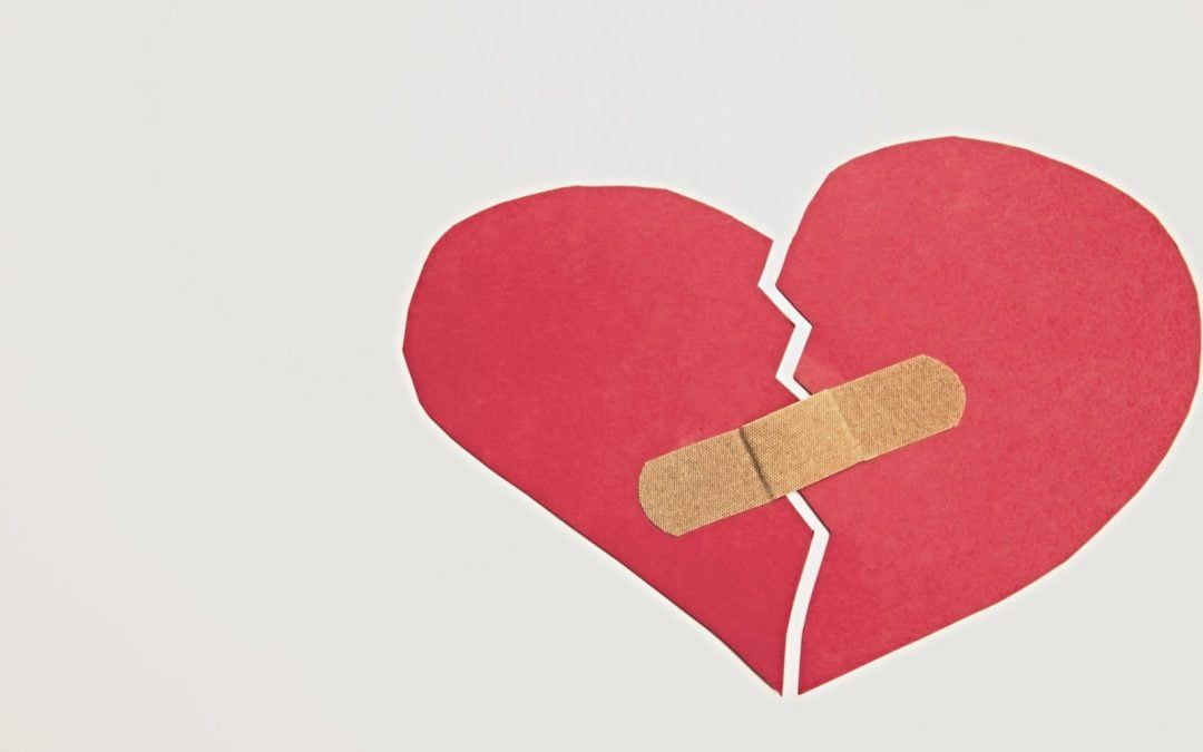 Torn construction-paper heart taped together with bandage