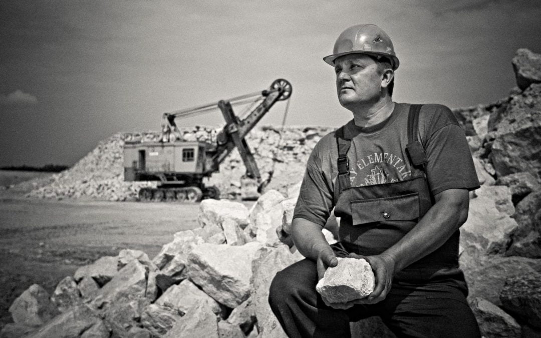 Laborer with hard hat resting in quarry