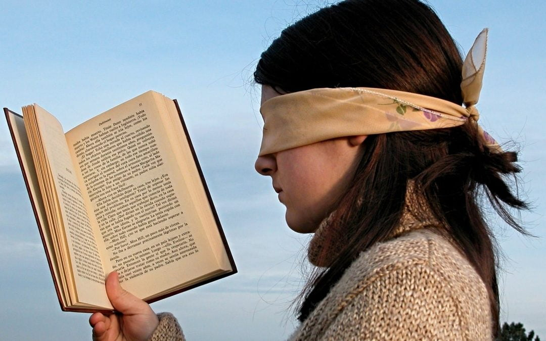 Blindfolded girl holding open book