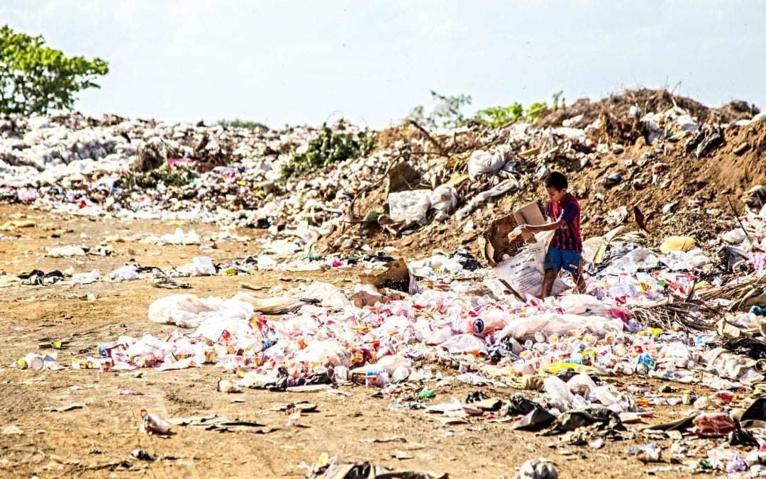 Boy carrying cardboard box walking through trash dump