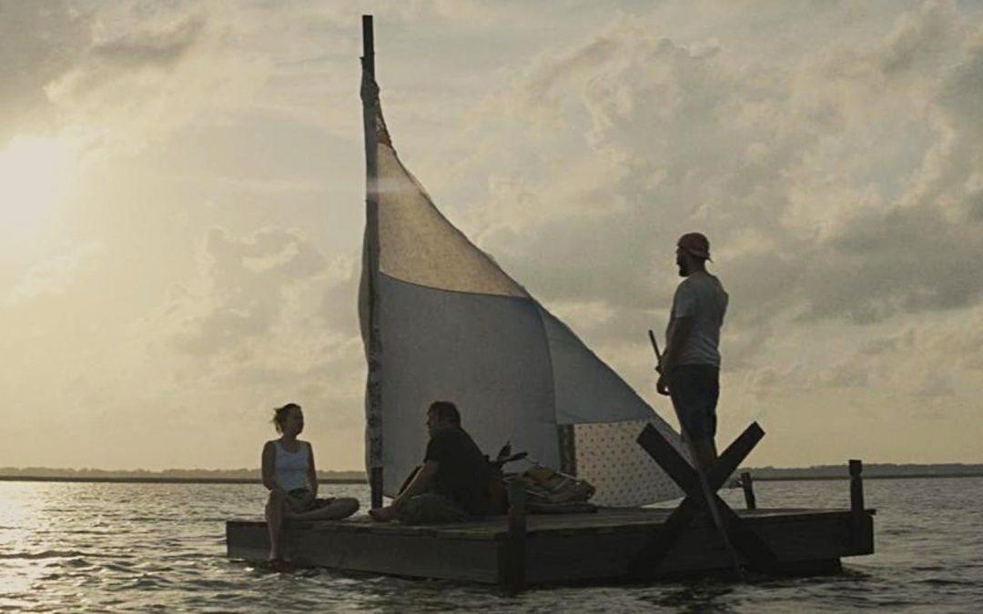 Three people on sailboat in ocean