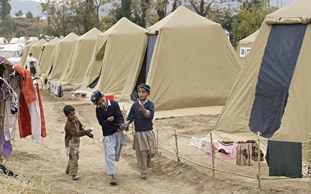 Boys in refugee camp with tents