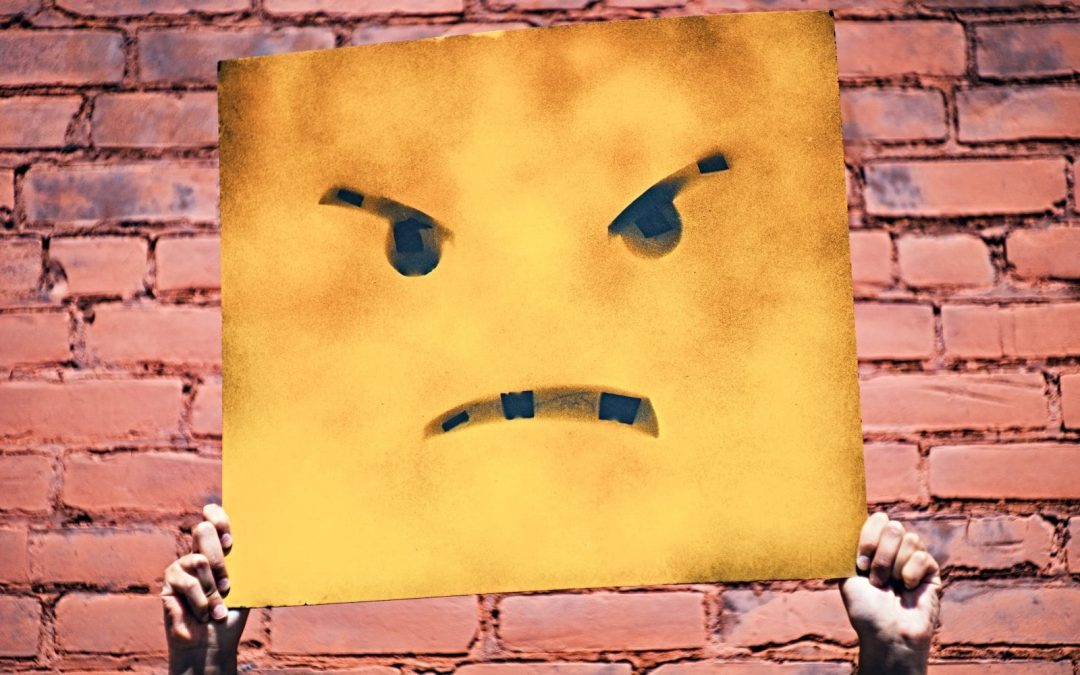 Someone holding yellow sign with angry face in front of brick wall