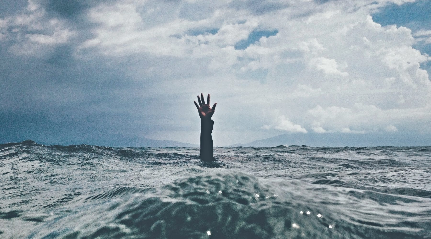 Arm raising up out of stormy sea