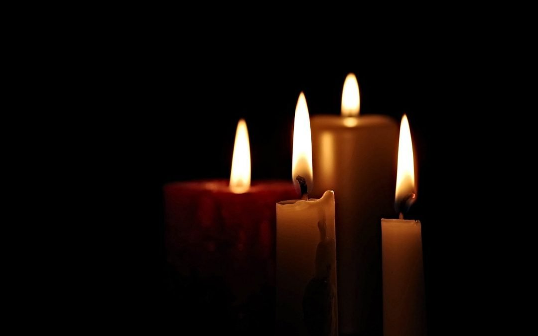 Four candles lit in darkness
