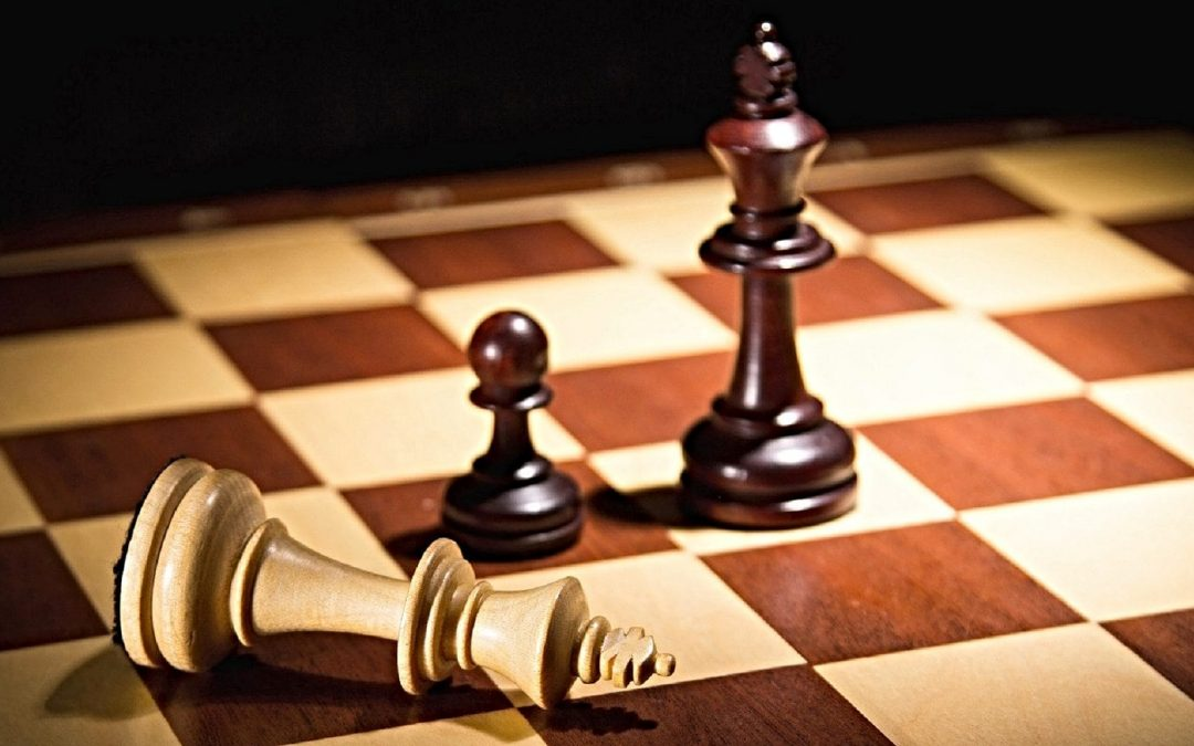 Chess king laying on side on chessboard