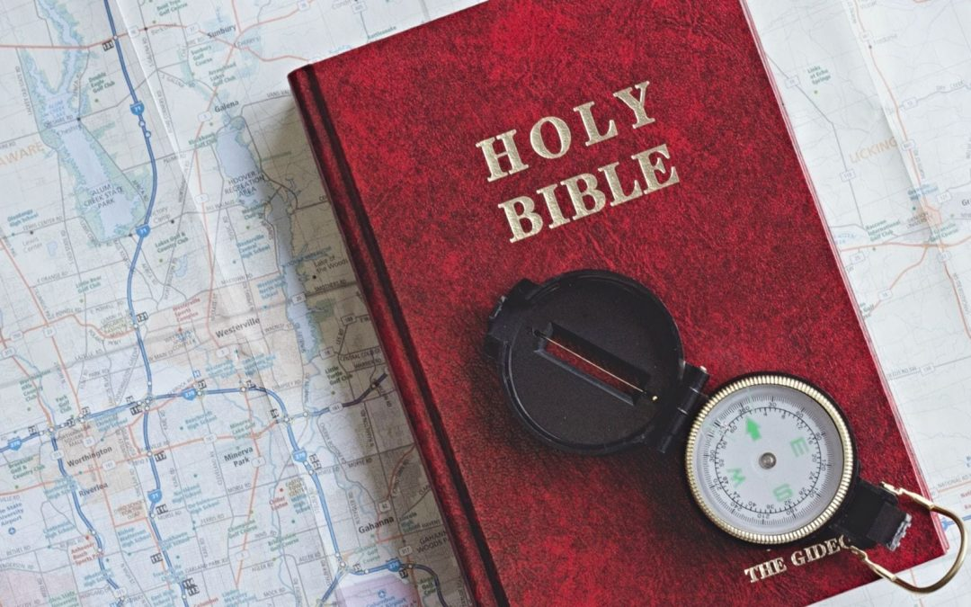 Compass and Bible resting on map