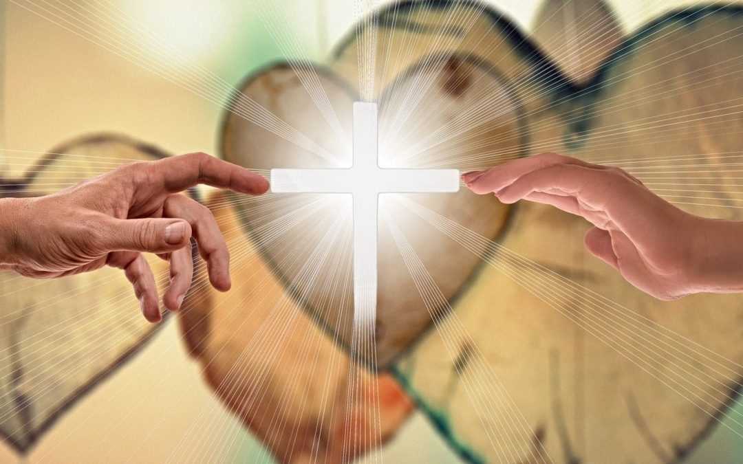 Two hands touching white cross with hearts in background