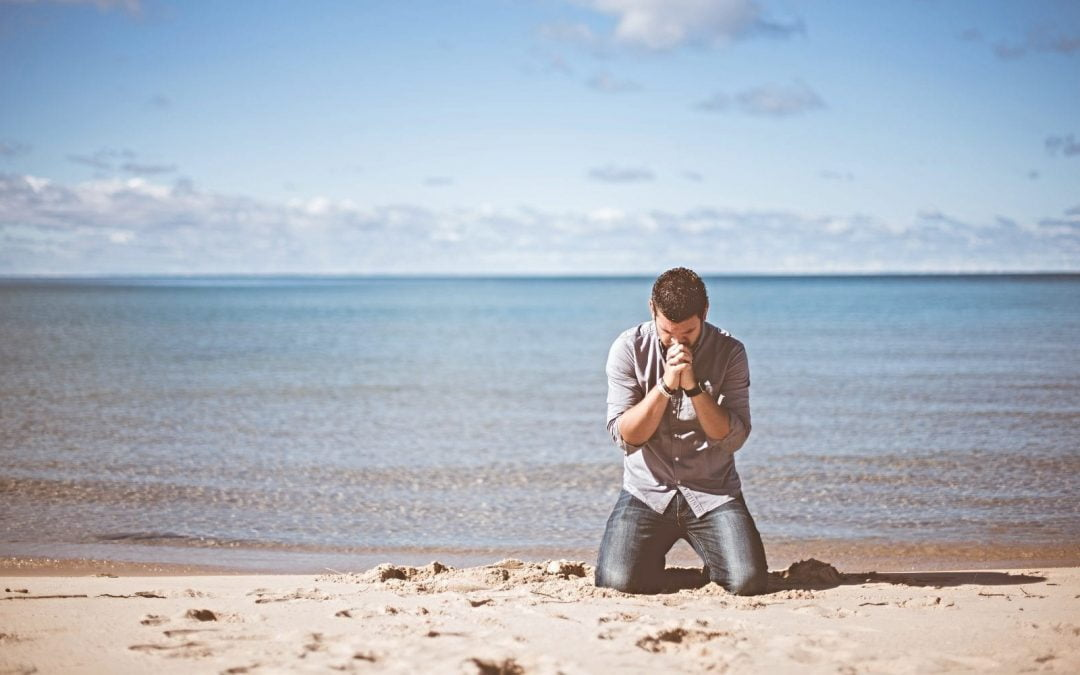 Kneeling man praying on shoreline