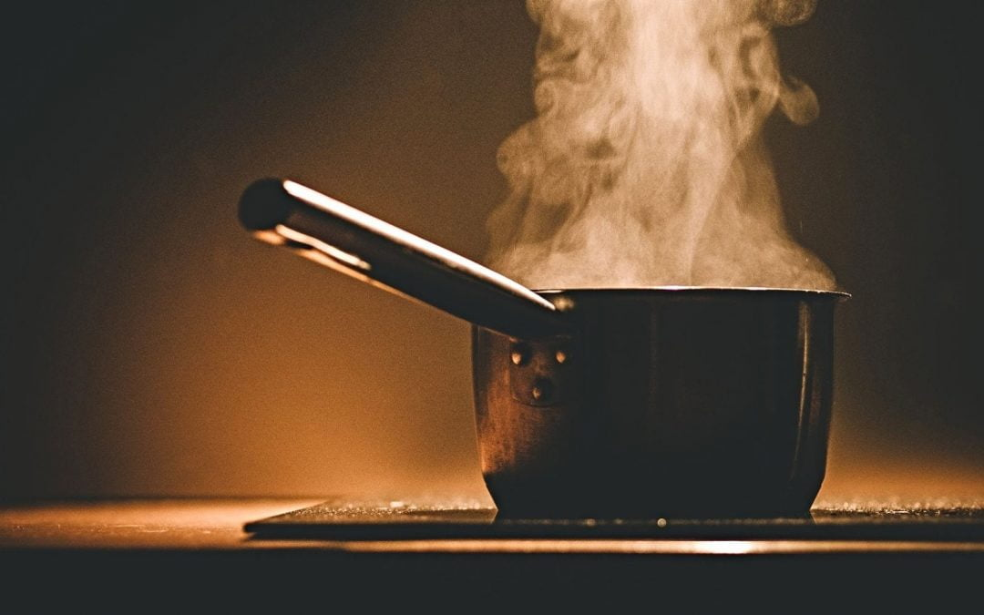 Pot on stovetop with steam wafting out