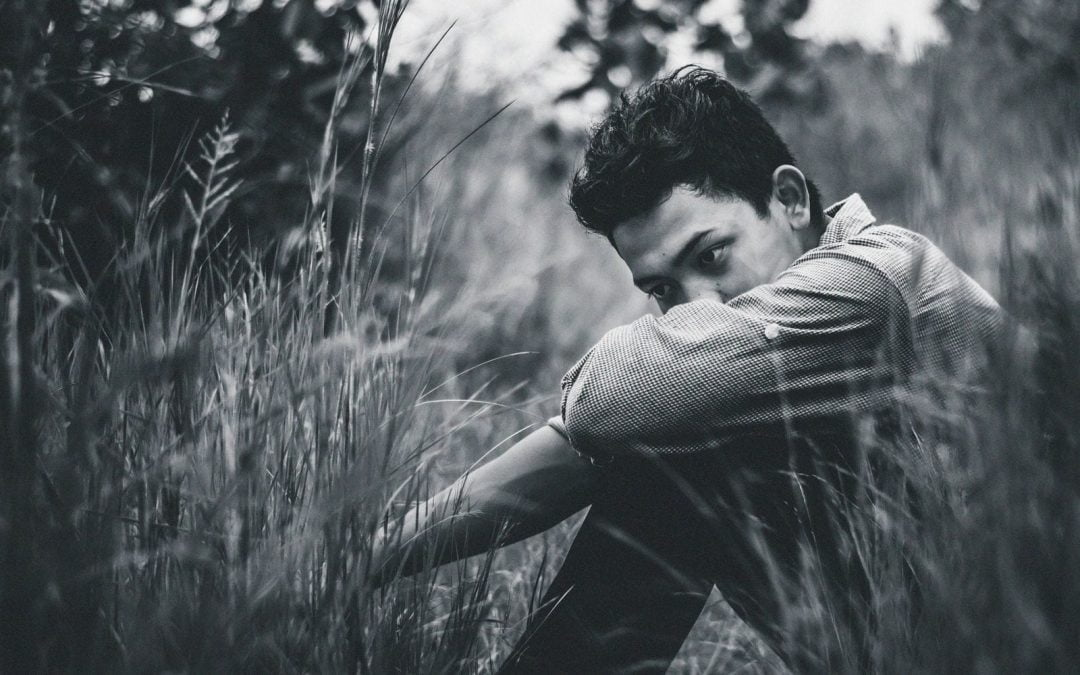 Sad teen boy sitting in grassy field