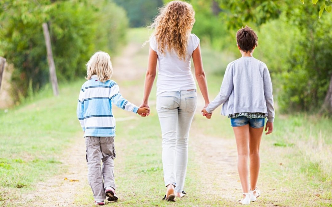 Mom walking on path holding hands with and flanked by two kids