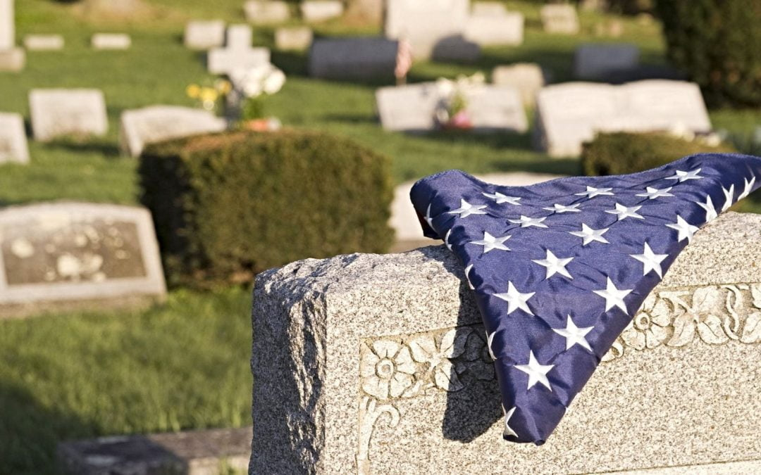 Folded flag draped over tombstone in cemetery
