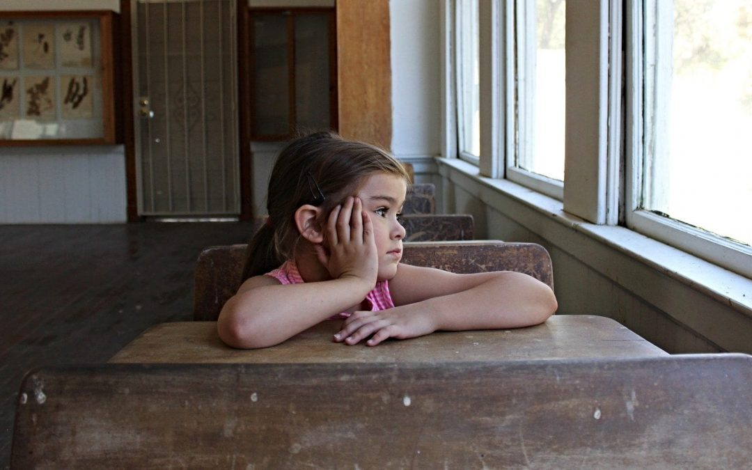 Sad girl looking out window from school classroom