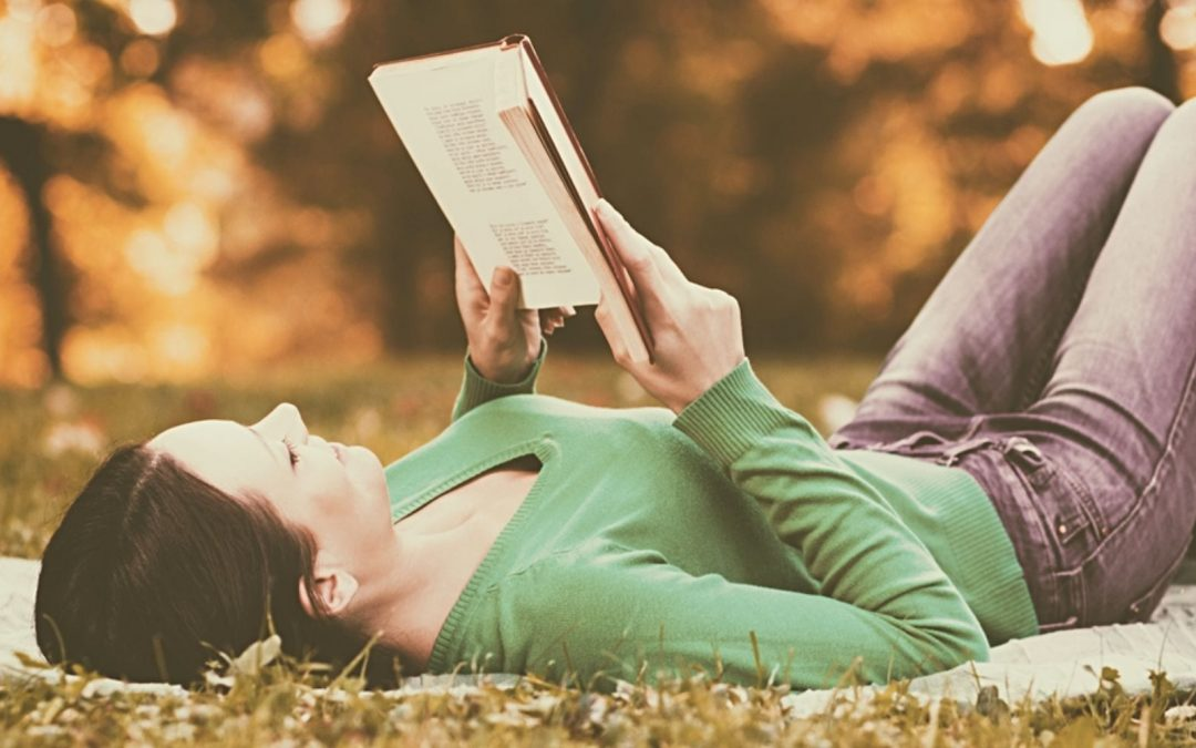 Woman reclining on the ground reading a book