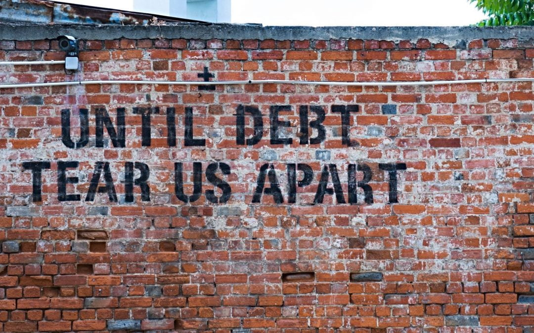 Graffiti about debt written on brick wall